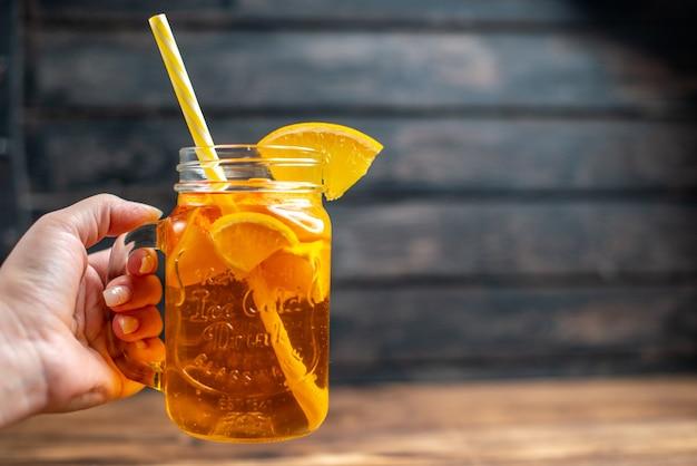正面から見た新鮮なオレンジ ジュースは、暗いバーのフルーツ カラー写真カクテル ドリンクの空きスペースの缶