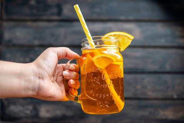 Свежий апельсиновый сок, вид спереди, внутри банки на темном баре, цветная фотография фруктов, коктейльный напиток