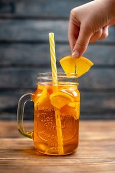 Свежий апельсиновый сок, вид спереди, внутри банки с соломкой на темном баре, коктейльный напиток фруктового цвета