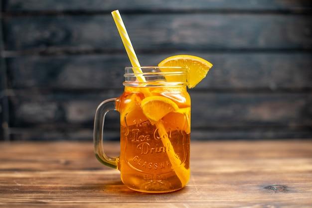 Свежий апельсиновый сок, вид спереди, внутри банки с соломкой на темном баре, цвет фруктов, фото, коктейльный напиток