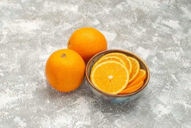 Вид спереди свежие нарезанные апельсины и целые спелые фрукты на белом фоне сок цитрусовых экзотических тропических фруктов