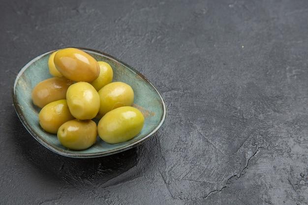 Vista frontale delle olive verdi organiche fresche su un piatto blu su un fondo nero