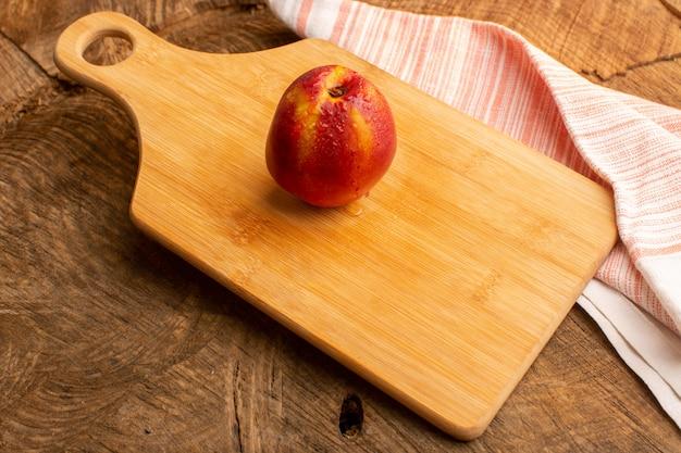 木製の机の上の正面の新鮮な桃