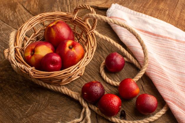 木製の机の上の正面の新鮮な桃と梅