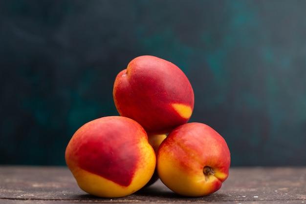 Vista frontale pesche fresche deliziosi frutti dolci sulla superficie blu scuro succo di frutta bevanda dolce fresco