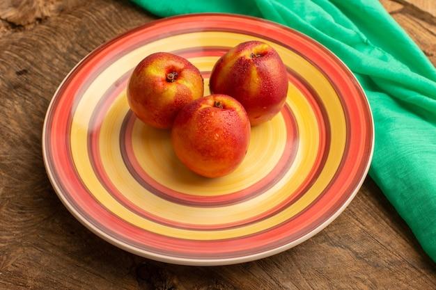 木製の机の上のカラフルなプレート内の正面の新鮮な桃