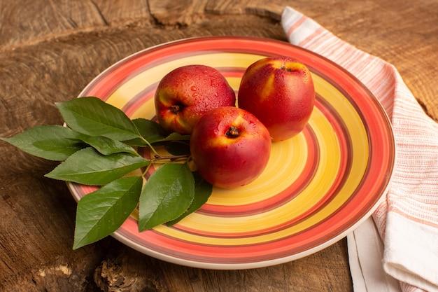 Вид спереди свежие персики внутри красочной тарелки на деревянном столе