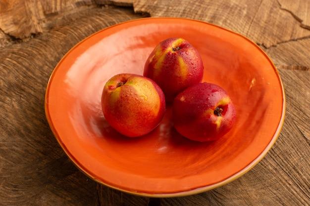 Вид спереди свежие персики внутри оранжевой тарелки на деревянном столе