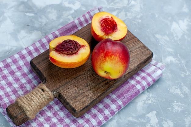 正面図新鮮な桃のまろやかでおいしい果物を明るい白い机の上でスライス