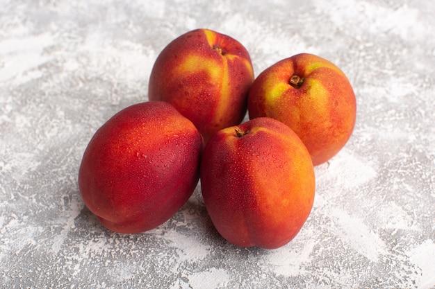 Вид спереди свежие персики сладкие и спелые, изолированные на белом фоне