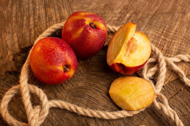 正面の新鮮な桃全体と木製の机の上でスライス