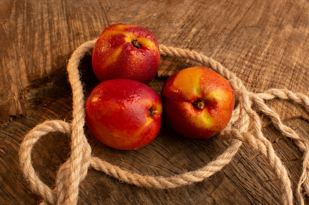 Front view fresh peaches with ropes on wooden desk fruit color summer
