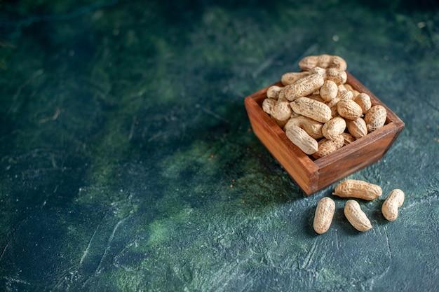 Vista frontale arachidi fresche su noci blu scuro snack alla nocciola cips foto a colori di noce