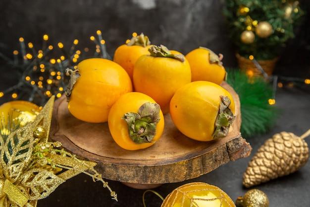 暗い背景のフルーツトロピカルエキゾチックなフレッシュジュースのクリスマスのおもちゃの周りの正面図新鮮な柿
