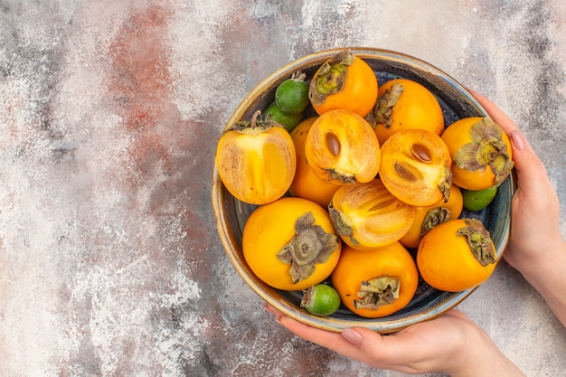 Front view fresh persimmons feijoas in a bowl in female hand on nude background