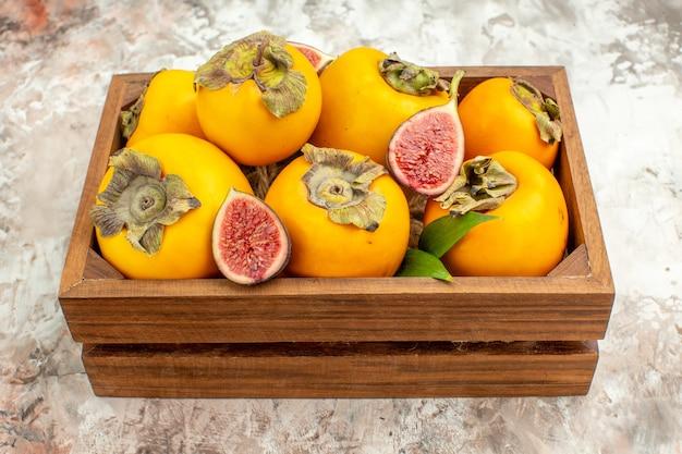 孤立した背景の木製の箱に新鮮な柿のイチジクの正面図