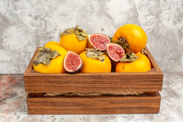 Front view fresh persimmons figs in wooden box on nude
