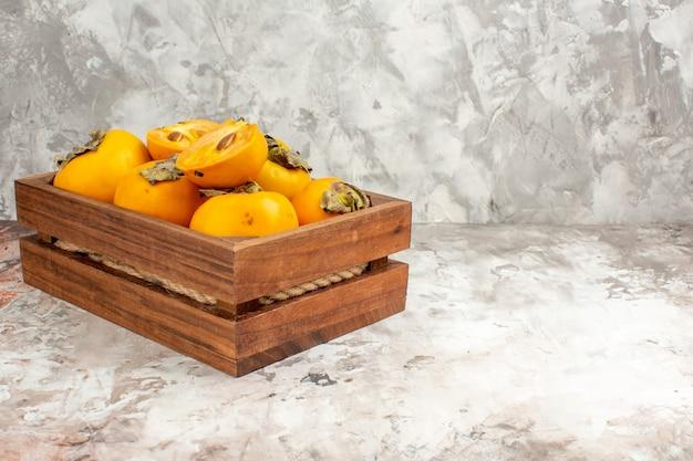 裸の背景の空きスペースに木製の箱で新鮮な柿の正面図