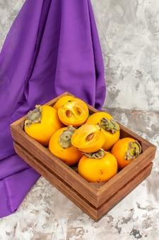 ヌードの後ろに木製の箱の紫色のショールで新鮮な柿の正面図