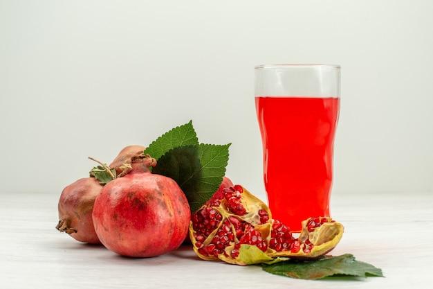 흰색 책상에 신선한 석류와 전면보기 신선한 석류 주스