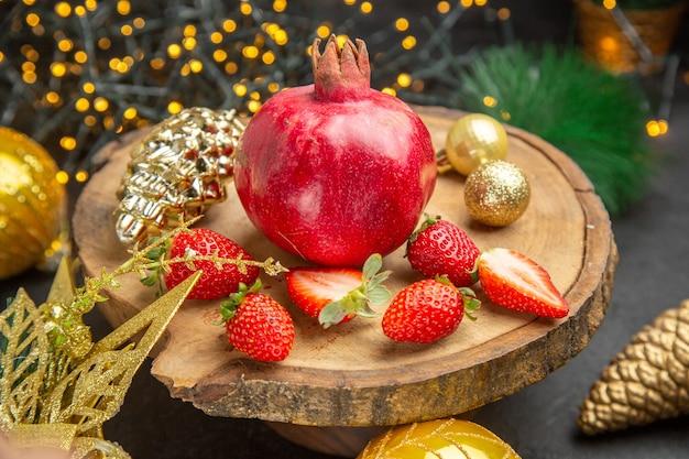 暗い背景色の写真クリスマスホリデーフルーツのクリスマスのおもちゃの周りにイチゴと新鮮なザクロの正面図