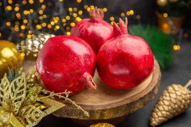 暗い背景色の写真クリスマスホリデーフルーツのクリスマスのおもちゃの周りの新鮮なザクロの正面図