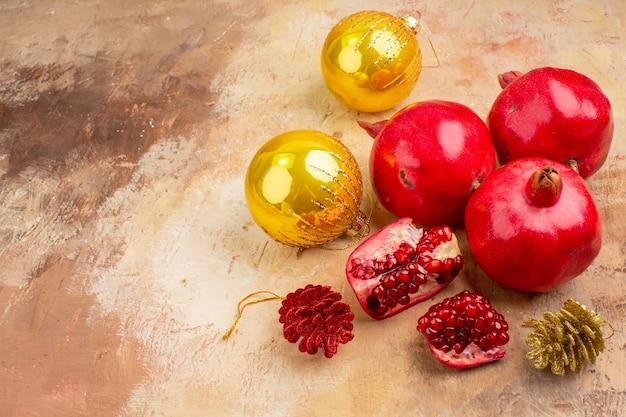Melagrane fresche di vista frontale con i giocattoli dell'albero di natale su succo di frutta della foto di colore di sfondo chiaro morbido