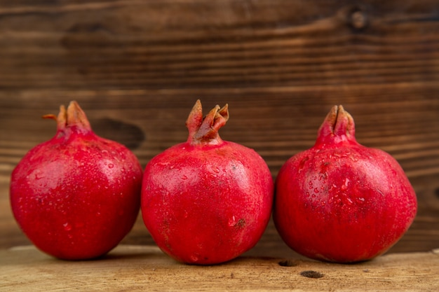 Front view fresh pomegranates on wooden desk color fruit juice photo tree red