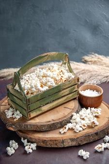 Vista frontale popcorn freschi sul cibo di mais popcorn snack superficie scura