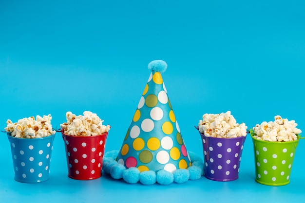 A front view fresh popcorn inside colorful baskets along with birthday cap on blue, movie cinema snack corn