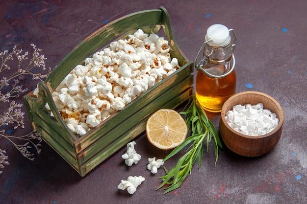 Vista frontale popcorn freschi con limone e olio su mais di olio di film snack superficie scura
