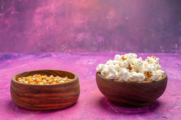 ピンクのテーブルコーン映画シネマカラーに生のトウモロコシと正面図新鮮なポップコーン