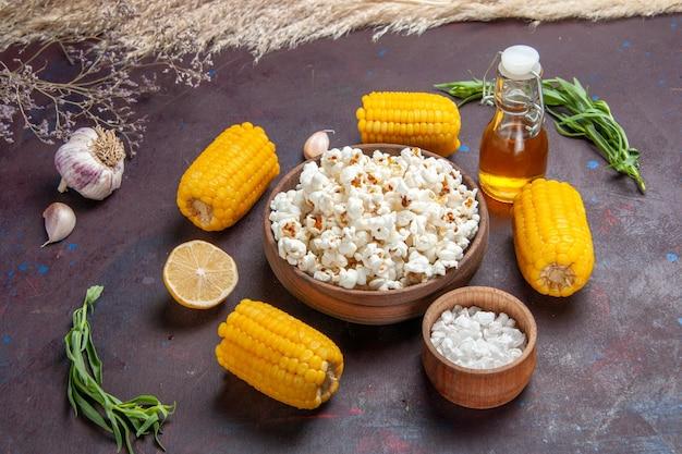 Vista frontale popcorn fresco con semi gialli crudi e olio su pianta di film di mais popcorn snack superficie scura