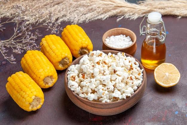 Vista frontale popcorn fresco con semi gialli crudi e olio su pianta di film di mais popcorn snack superficie scura dark