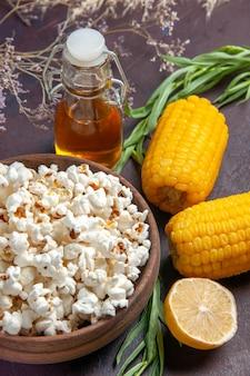 暗い表面のスナックポップコーンコーン映画工場で生の黄色いトウモロコシと正面図新鮮なポップコーン
