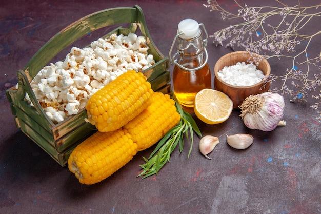 Vista frontale popcorn freschi con semi gialli su popcorn di olio di film snack di mais superficie scura