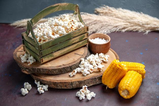 Vista frontale popcorn fresco con calli gialli sulla superficie scura snack popcorn cibo di mais