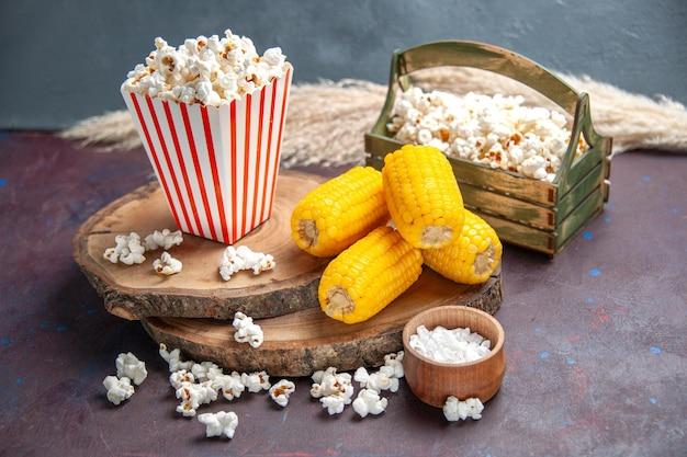 Vista frontale popcorn fresco con calli gialli sulla superficie scura snack popcorn cibo mais