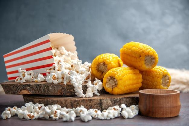 Vista frontale popcorn fresco con calli a fette gialli sulla superficie scura snack popcorn cibo mais