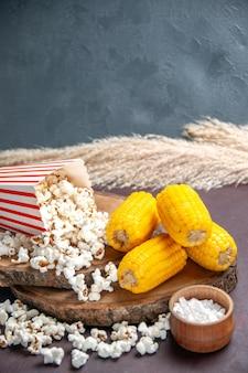正面図新鮮なポップコーンと黄色のスライスしたトウモロコシが暗い表面にスナックポップコーンフードコーン