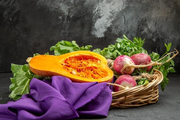 Zucca fresca vista frontale con verdure e ravanello sul tavolo grigio