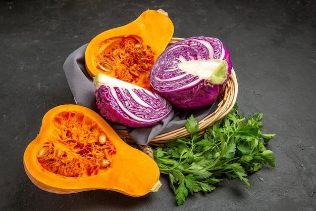 Zucca fresca vista frontale con verdure e cavolo rosso sul tavolo scuro