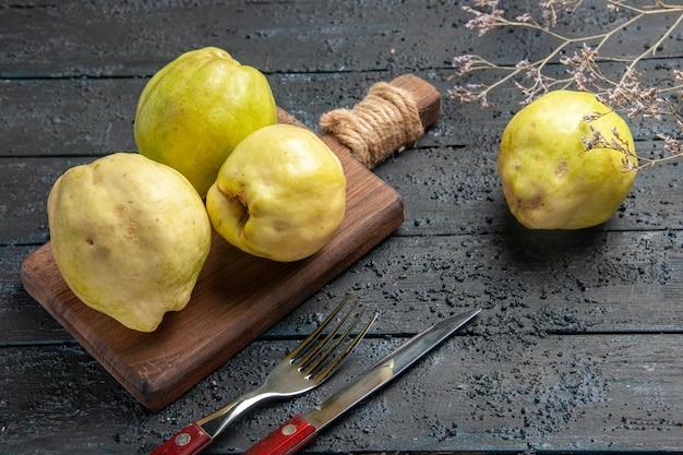 正面図紺色の机の上の新鮮なマルメロのまろやかで酸っぱい果物は熟した新鮮な酸っぱい果樹を植えます
