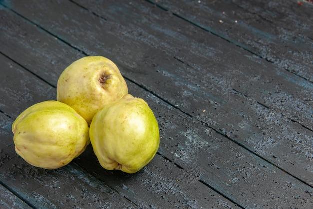 Front view fresh quinces mellow and sour fruits on a dark-blue desk ripe fetus fresh tree sour plant fruit