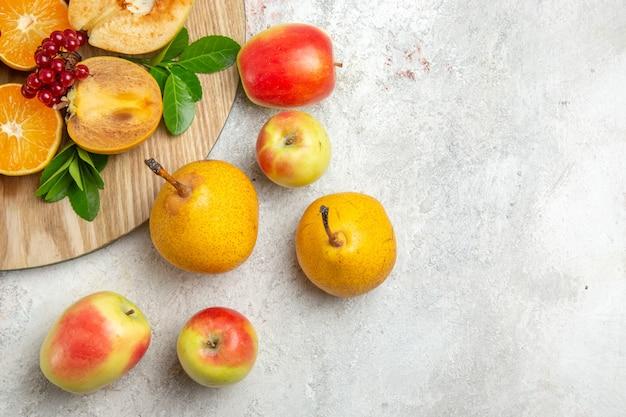 밝은 흰색 테이블에 다른 과일과 함께 신선한 모과가 있는 전면 보기 잘 익은 과일 부드러운 신선한