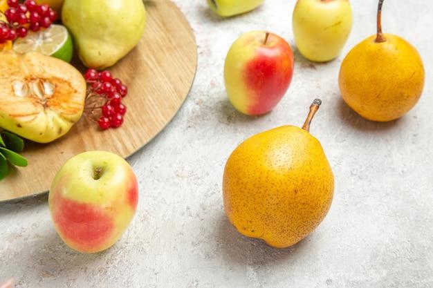 白いテーブルの上に他の果物と一緒に新鮮なマルメロの正面図熟した果物新鮮なまろやか