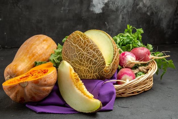 正面図新鮮な大根とカボチャとメロンのダークテーブルの新鮮な熟したサラダ