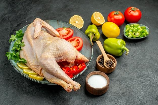 Вид спереди свежая сырая курица с зеленью, лимоном и овощами на темном фоне птица еда цвет мясо фото животное