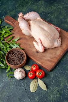 Vista frontale pollo crudo fresco con pomodori su cucina blu scuro ristorante pasto foto animale fattoria carne colore cibo pollo