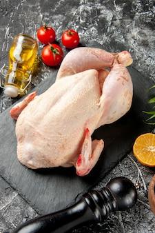 Vista frontale pollo crudo fresco con pomodori sul pasto da cucina chiaro-scuro foto animale carne di pollo colore fattoria cibo